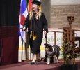 Shannon Smith, fine arts, walks along the stage with her dog in the Commencement Ceremony in Kay Yeager Coliseum Dec. 12, 2015