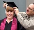 Sean Estrada helps his wife, Laura Estrada, English, put on her cap and fix her bangs while in the MPEC before Commencement Ceremony held in the Kay Yeager Coliseum, Dec. 12, where 440 crossed the stage. Photo by Rachel Johnson