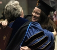 Astri Burgos, nursing, hugs her professors as she heads back to her seat after recieving her diploma case in the Kay Yeager Coliseum, Dec. 12. Photo by Rachel Johnson