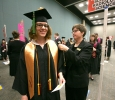 Bricelle Satterfield, office of registrar, helps Rachel Whatley, radiologic science, fix her gown at Midwestern State University graduation, May 16, 2015 at the Kay Yeager Coliseum. Photo by Rachel Johnson