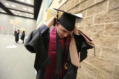 """Florian Regnery adjusts his academic gown for a master's degree at graduation, Dec. 16, 2017. """"I don't know what to expect,"""" Regnery said. """"I'm from Germany and we don't do this."""" Photo by Bradley Wilson"""