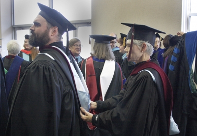Christopher D'Amico, lecturer, gets his scarf fixed by Liz Minden, instructor, at the fall 2017 commencement at the Kay Yeager Colliseum on Sat. Dec. 16, 2017. Photo by Justin Marquart