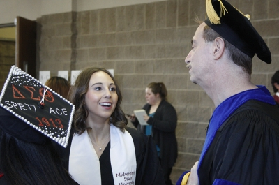 Kristen Gregg, BA graduate, and Jim Sernoe, chair and associate professor of mass communication, talk before the fall 2017 commencement at the Kay Yeager Colliseum on Sat. Dec. 16, 2017. Photo by Justin Marquart