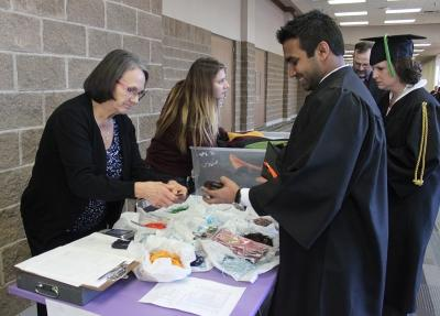 Tharusha Wanigasekera, mechanical engineer, buys his cap and tassle at the bookstore stand set up by where the graduates get lined up in the Multi-Purpose Entertainment Center the morning of Commencement, Sat. Dec. 16, 2017. Photo by Rachel Johnson