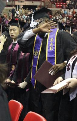 Valentine Atuchukwu, education, does a dab during the alma mater at the end of commencement in Kay Yeager, Sat. Dec. 16, 2017. Photo by Rachel Johnson