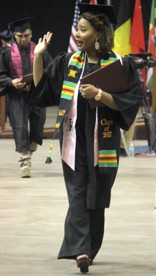 """Jasmine Moody, criminal justice, waives at people inthe audience as she walk back to her seat after walking the stage and receiving her degree in Kay Yeager Coliseum, Sat. Dec. 16, 2017. """" I didn't want to fall, that was my biggest concern, and I wanted to make sure I didn't blink in the middle of a photo and then you know the stairs. I want to give a shout-out to my mom,"""" Moody said. Photo by Rachel Johnson"""
