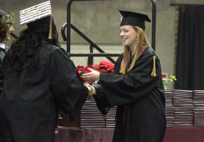 Emma Kate Winkles, education, is handed her degree as she cross the stage in Kay Yeager Coliseum, Sat. Dec. 16, 2017. Photo by Rachel Johnson