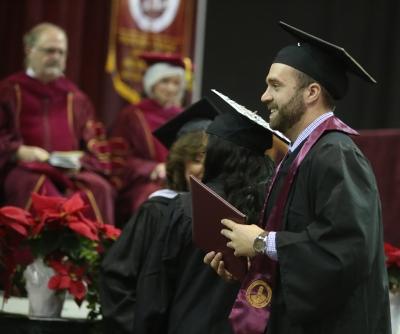 Noah Fazekas walks across stage at graduation, Dec. 16, 2017. Photo by Bradley Wilson