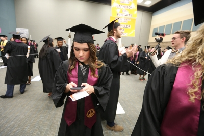 Olivia Zamora texts while waiting for candidates to line up at graduation, Dec. 16, 2017. Photo by Bradley Wilson
