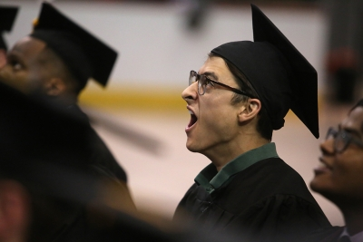 Michael Olaya, in the last row of graduates, yawns before the ceremony ends at graduation, Dec. 16, 2017. Photo by Bradley Wilson