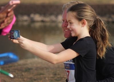Harper Gillen, 1 mile participant, takes a selfie with her dad Ryan Gillen, 1 mile participant, after finishing the Fantasy of LIghts 1 mile event, Dec. 2, 2017. Photo by Rachel Johnson