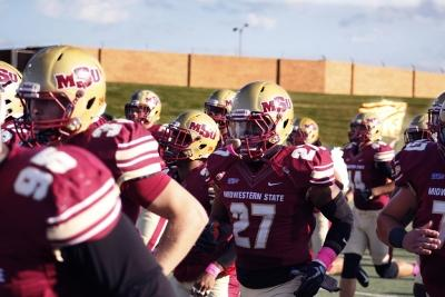 The football team runs onto the field beofre the football game at the Memorial Stadium where the Mustangs won 45-3 on Saturday, Oct. 21, 2017. Photo by Justin Marquart