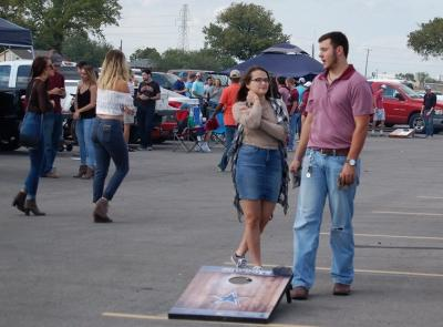 Madelyn Williams, undecided freshman, Christopher Balderas, pre-med freshman, play corn hole at homecoming tailgate on Saturday, Oct. 17, 2017. Photo by Shea James