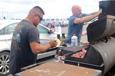 Pedro Rojo, cook for Junior League of Wichita Falls, and Robert Ross, cook for Junior League of Wichita Falls, cook for German pilots at the tailgate outside of Memorial Stadium before the Homecoming Game. Photo by Rachel Johnson