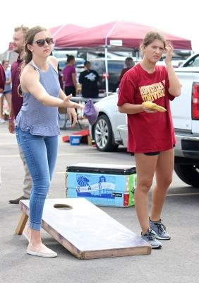 """Abigail Helms, nursing junior, and Abigail Gentry, finance junior, play corn hole at the Tailgate outside of Memorial Stadium for the Homecoming game, Saturday Oct 21, 2017. """"It's fun meeting new people and hanging out with everyone in Greek Life,"""" Helms said.Photo by Rachel Johnson"""