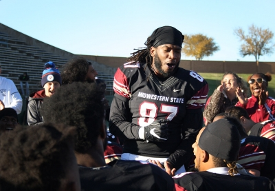 Dorian Johnson, kinesiology and sports and leisure senior, gives a shout out at the beginning of the group huddle after MSU shook hands with University of Sioux Falls players after the Round One NCAA II Playoff game where MSU won 24-20. Photo by Rachel Johnson