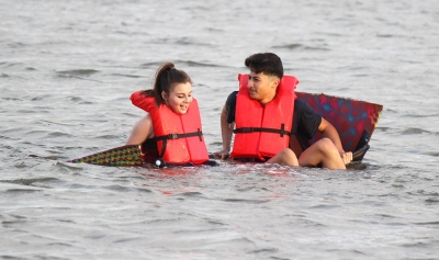Javier Suarez, mass communication sophomore, and MIa Heck, mass communication sophomore, rest on their sinking boat for Chi Omega and Sigma Alpha Epsilon during the Homecoming Boat Race Friday Oct. 20, 2017. Photo by Rachel Johnson