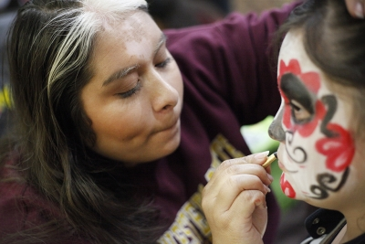 Rutth Mercado, mass communication junior, paints Fatima Chavez, attendee, face during the Dia de los Muertos event held by multiple organizations in the Atrium, Wednesday, Nov. 1, 2017. Photo by Francisco Martinez