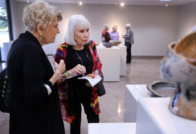 Anne-Marie Williamson, artist in Empty Bowls, and Lee Williamson, her son, look at the other bowls that were entered into the Empty Bowls Gallery Oct. 5 before the juror announces the winner of the competition. Photo by Rachel Johnson
