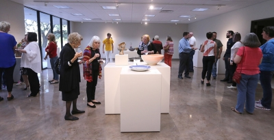People look at the different bowls created by different artists at the Empty Bowls Gallery Reception held at the Wichita Falls Museum of Art at MSU Oct. 5. Photo by Rachel Johnson