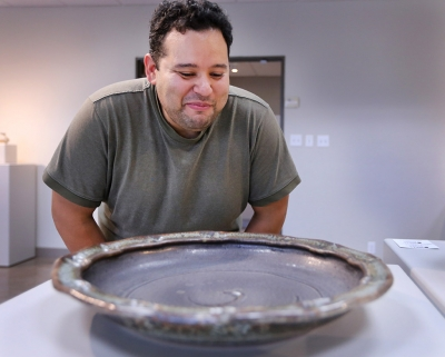 "Alberto Veronica, creator of ""Peachy Bowl"" piece, admires other artist's bowls during the Empty Bowls Gallery in the Wichita Falls Museum of Art at MSU Oct. 5. Photo by Rachel Johnson"