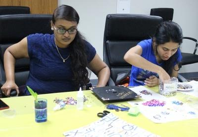 Tejaswi Singam, computer science masters, and Tejaswini Wootkuri, computer science masters, decorate their caps for graduation during Finals Frenzy, Thurs. Dec. 7, 2017. Photo by Rachel Johnson
