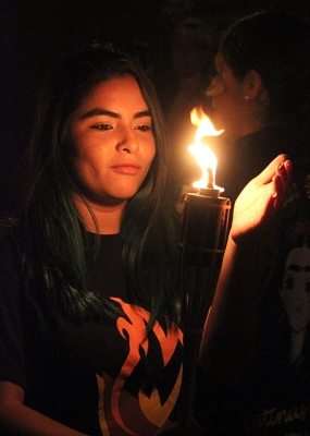 Conney Vargas, marketing senior, holds her hand infront of the flame as she walks towards to front of the parade being one of the first to get her torch lit at the Torchlight Parade tradition apart of MSU Homecoming, Thursday, Oct. 19, 2017. Photo by Rachel Johnson