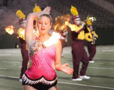 Alexis Maggard, special education freshman, twirls her baton that is on fire around her shoulders as a part the Golden Thunder Marching Band's halftime performance titled 'Changing Channels' Oct. 7. Photo by Rachel Johnson