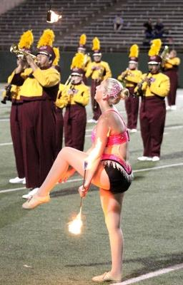 "Alexis Maggard, spech education freshman, shows off her hair ribbon while she tosses her lit batons in the air as the band performs ""Changing Channels"" for the Texas A&M Commerce vs MSU football game held at the Memorial Stadium, Oct. 7. Photo by Marissa Daley"