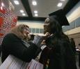Jessica Gallant, Office of Registrar, helps Omozuwa Omigie, nursing, with her gown at Midwestern State University fall graduation, Dec. 13, 2014 in Wichita Falls, Texas. Photo by Rachel Johnson