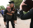 Chelsey Wall, special education, gets on her dad's back, Andrew Wall, for a piggy back picture after Commencement May 14, hed in the Kay Yeager Coliseum. Photo by Rachel Johnson