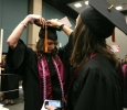 Mae Johnson, nursing, gets help from Deborah Roucloux, nursing, to fix her cap while waiting for Commencement to start at the MPEG, May 14. Photo by Rachel Johnson