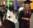 Taylor Coffman, mass communication, chuckles while reading Harley Warrick's mortar board at Midwestern State University graduation, May 14. This was the first year graduates have been allowed to decorate their hats. Photo by Bradley Wilson