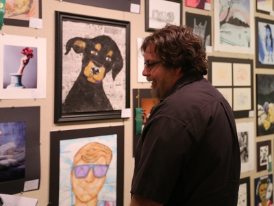 From Lewisville, Andy Longo, whose daughter compete in the show, looks at artwork at the opening of the MWSU High School Art Show, Feb. 3, 2018. Photo by Treston Lacy