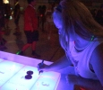 Emily Burns, theatre freshman, drawing on the shuffleboard table at the GloCade in the DL Ligon Coliseum on Aug 24. Photo by Kayla White.