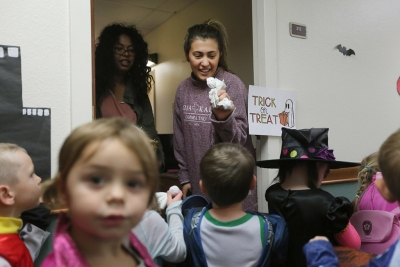 Dea Vukataha, biology sophomore, passes out candy while her roommate, Shakira Hernandez, biology freshman, looks on while the kids of YMCA trick or treat in Killingsworth Residence Hall at Midwestern State University. Photo by Justin Marquart