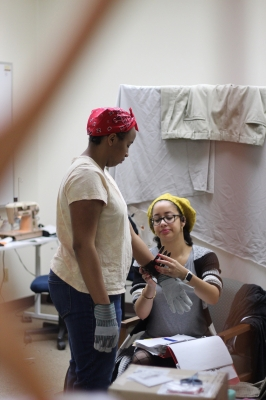 Nicole Smalls is helped by Kaylor Winter-Roach to put on her wrist leather bands on Jan. 16, 2018. Photo by: Leo Gonzalez.