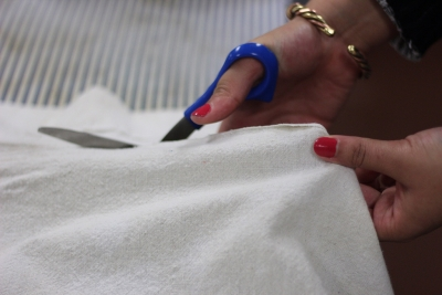 """Julia Lucas cuts fabric in preparatoion for """"Urinetown"""" on Feb. 16 Photo by: Leo Gonzales"""