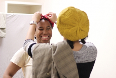 Nicole Smalls getting her bandana tied by Kaylor WInter-Roach for one of her characters on Urinetown on Feb. 8, 2018. Photo by: Leo Gonzalez.