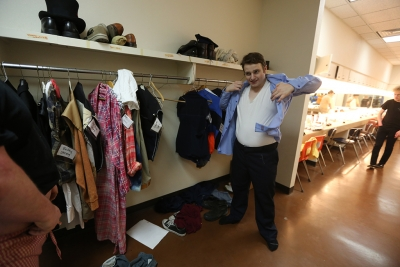 """Jon Stone puts on his police officer costume before the first dress rehearsal of """"Urinetown,"""" Feb. 18. Photo by Bradley Wilson"""