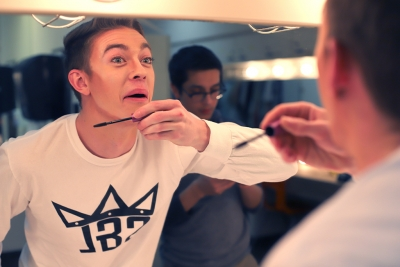 Samuel Mitchell applys mascara for the first time in his life for Urinetown in the dressing room on Feb. 16, 2018. Photo by Sarah Graves