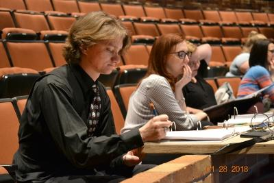 """Ron Harle, theater freshman, reads a line from his notebook to an actor in the Fain Fine Arts Auditorium Jan. 28, 2018 during rehearsal for """"Urinetown."""" Photo by Robin Reid"""