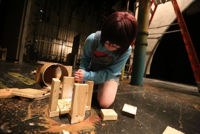 """Shae Dorsman helps to take down the set of """"Urinetown."""" Photo by Bradley Wilson"""