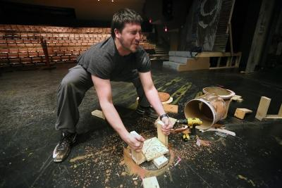 """Ben Ashton helps to destroy some of the set plumbing while taking down the set of """"Urinetown."""" Photo by Bradley Wilson"""