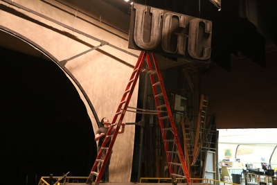 "Ben Ashton helps to take down the set of ""Urinetown."" Photo by Bradley Wilson"