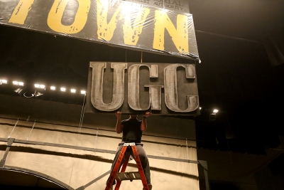 """Ben Ashton helps to take down one of the signs while other crew members take down the set of """"Urinetown."""" Photo by Bradley Wilson"""
