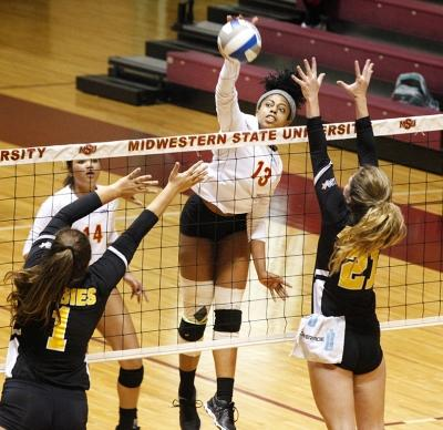 Aerielle Edwards, applied arts & aciences senior, jumps up to spike the ball towards Cameron University opponents during the volleyball game in D.L. Ligon Coliseum on Nov. 9, 2017. Photo by Harlie David