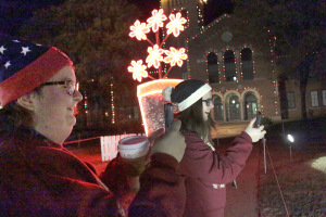 Kinsey McCloud, undeclared freshmen, and Morgan Sinclair, sociology freshmen, take a pictures of the Fantasy of Lights displayed in front of the Hardin Administration Building on Nov. 30. Photo by Kayla White.