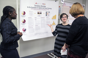 Accounting and sociology senior Careisha Whyte and junior Catherine Stepniak talk to spectators at the poster presentations Thursday. The two won first place for their poster presentation. Photo by Topher McGehee