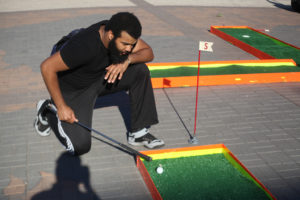 John Smith, psychology junior, tees up on the mini-golf course at spring Finals Frenzy on the Jesse Rodgers Promanade on May 4, 2017. File photo by Timothy Jones.